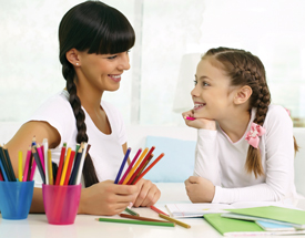 Smiling parent and child sitting a desk with colored pencils and papers