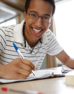 Smiling student writing in a notebook