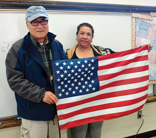 Two smiling ESL students holding the US flag